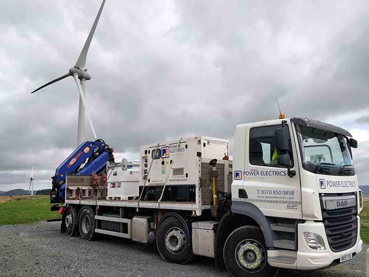 Generator on lorry with wind turbine in the background